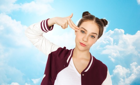 clouds making: people, emotion, expression, stress and teens concept - bored teenage girl making headshot by finger gun gesture over blue sky and clouds background
