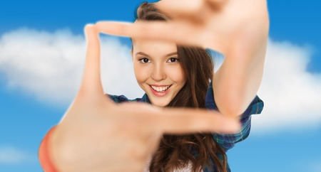 clouds making: people and teens concept - happy smiling pretty teenage girl making frame of fingers over blue sky and clouds background Stock Photo