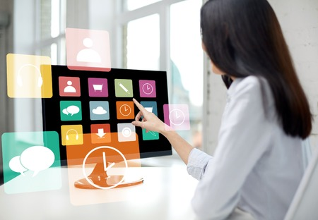 online education: business, people, technology and education concept - close up of woman pointing finger to application icons on computer monitor in office Stock Photo