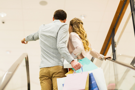 showing: sale, consumerism and people concept - happy young couple with shopping bags raising up by escalator and pointing finger in mall