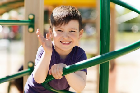 young boy smiling: summer, childhood, leisure, gesture and people concept - happy little boy waving hand on children playground climbing frame Stock Photo
