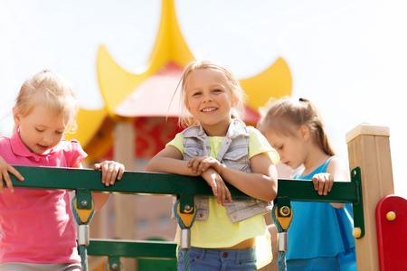 zomer, jeugd, vrije tijd, vriendschap en mensen concept - gelukkig weinig meisjes op speelplaats voor kinderen klimrek Stockfoto