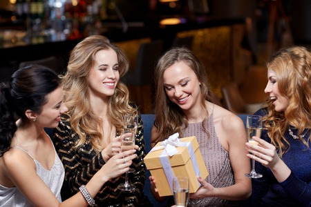 sektglas: celebration, friends, bachelorette party, birthday and holidays concept - happy women with champagne glasses and gift box at night club