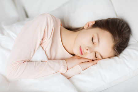 asleep: people, children, rest and comfort concept - girl sleeping in bed at home
