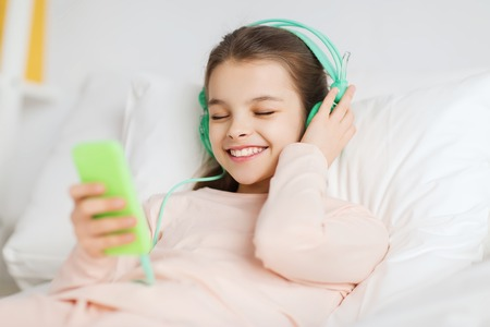 child in bed: people, children, rest, and technology concept - happy smiling girl lying awake with smartphone and headphones in bed listening to music at home Stock Photo