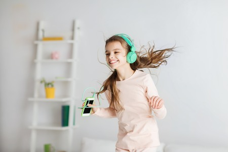 girl home: people, children, pajama party and technology concept - happy smiling girl in headphones jumping on bed with smartphone and listening to music at home