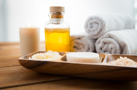 massage oil: beauty, spa, body care, natural cosmetics and bath concept - close up of soap with himalayan salt and scrub in wooden bowl on table