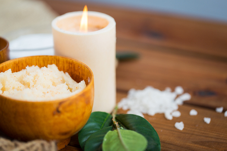 natural therapy: beauty, spa, therapy, natural cosmetics and wellness concept - close up of body scrub and candle on wood Stock Photo