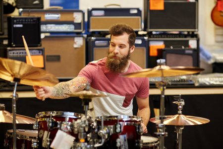 cymbals: music, sale, people, musical instruments and entertainment concept - male musician playing cymbals on drum kit at music store