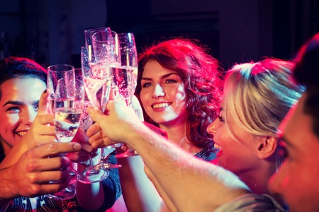 tomando alcohol: fiesta, días de fiesta, celebración, vida nocturna y la gente conceptuales - amigos sonrientes con copas de champán en el club Foto de archivo