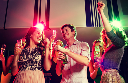 man drinking beer: party, holidays, celebration, nightlife and people concept - smiling friends clinking glasses of champagne and beer in club Stock Photo
