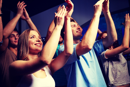 party, holidays, celebration, nightlife and people concept - smiling friends applauding at concert in club