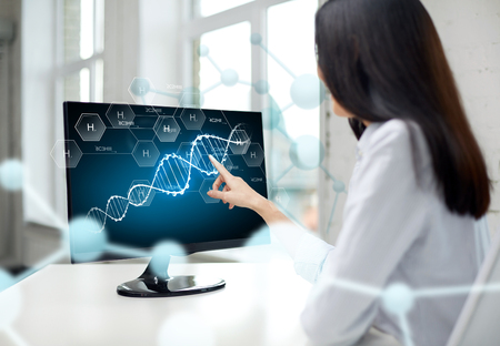 people, technology, biology, genetics and science concept - close up of woman pointing finger to dna molecule on computer monitor in office Stockfoto