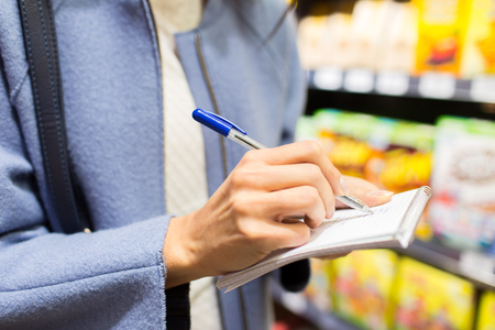 consumerism: sale, shopping, consumerism and people concept - close up of young woman with pen taking notes to notebook in market
