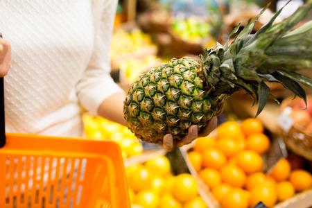 frutas tropicales: venta, compras, consumismo y el concepto de la gente - cerca de la mujer joven con canasta de alimentos y piña en el mercado de comestibles