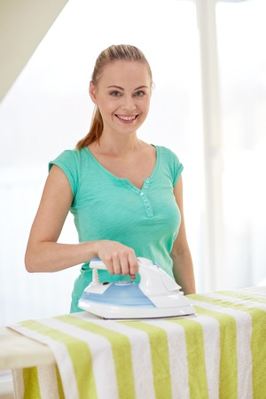 manuals: people, housework, laundry and housekeeping concept - happy woman with iron and ironing board at home