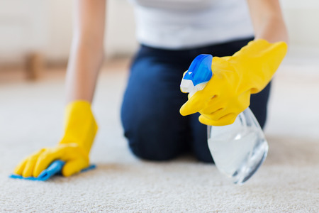 cleaning: people, housework and housekeeping concept - close up of woman in rubber gloves with cloth and detergent spray cleaning carpet at home