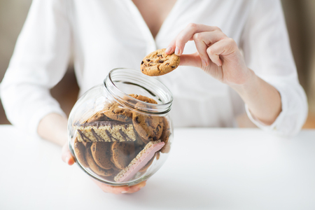 close up food: people, junk food, culinary, baking and unhealthy eating concept - close up of hands with chocolate oatmeal cookies and muesli bars in glass jar