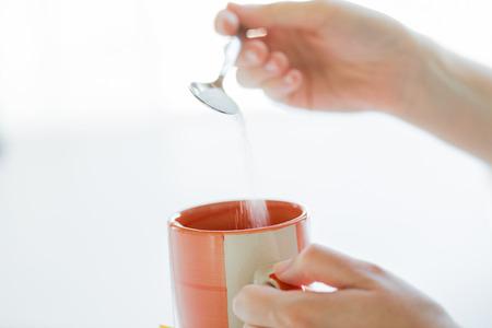 comida, comida basura, las bebidas y la alimentación poco saludable concepto - cerca de las manos de mujer con una cuchara de añadir azúcar a la taza de té