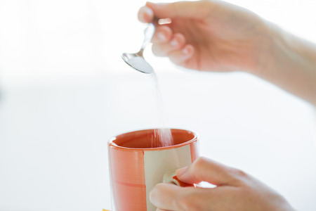 white sugar: food, junk-food, drinks and unhealthy eating concept - close up of woman hands with spoon adding sugar to tea cup