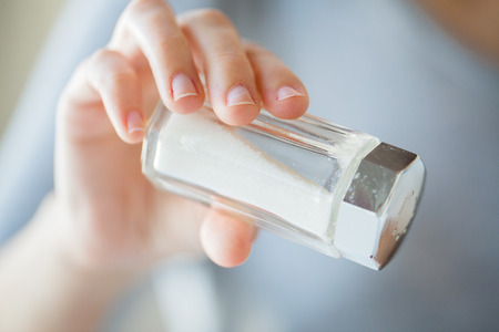 sal: comida, comida basura, la cocina y la alimentación poco saludable concepto - cerca de la mano que sostiene salero blanco
