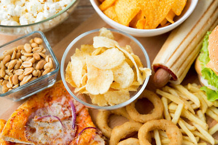 eating popcorn: fast food and unhealthy eating concept - close up of different fast food snacks on wooden table Stock Photo