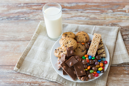 chocolate candy: junk food, sweets and unhealthy eating concept - close up of candies, chocolate, muesli and cookies with milk glass on plate