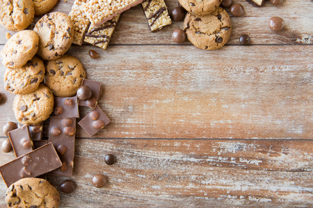 biscuits: junk food, sweets and unhealthy eating concept - close up of candies, chocolate, muesli and cookies on plate Stock Photo