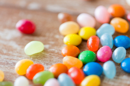 jelly beans: food, junk-food, confectionery and unhealthy eating concept - close up of multicolored jelly beans candies on table