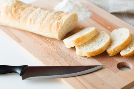 cuchillo de cocina: food, junk-food, diet and unhealthy eating concept - close up of white bread or baguette and kitchen knife on wooden cutting board Foto de archivo
