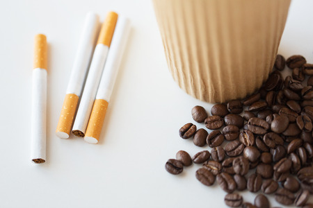 unhealthy lifestyle: bad habits, addiction and unhealthy lifestyle concept - close up of cigarettes, coffee cup and beans on table