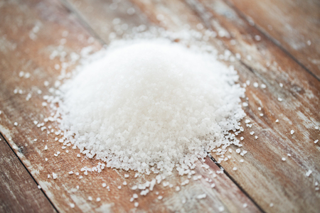 heap: food, junk-food, cooking and unhealthy eating concept - close up of white sea salt heap on wooden table