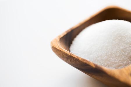 azucar: comida, comida basura, la cocina y la alimentación poco saludable concepto - cerca de blanco montón de azúcar en un tazón de madera