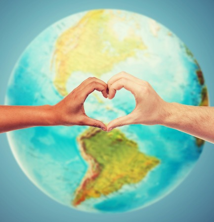 love of planet: people, peace, love, life and environmental concept - close up of human hands showing heart shape gesture over earth globe and blue background