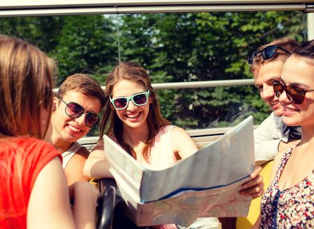looking out: friendship, travel, vacation, summer and people concept - group of smiling friends with map traveling by tour bus
