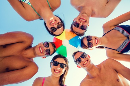 friendship, happiness, summer vacation, holidays and people concept - group of smiling friends wearing swimwear standing in circle with beach ball over blue sky