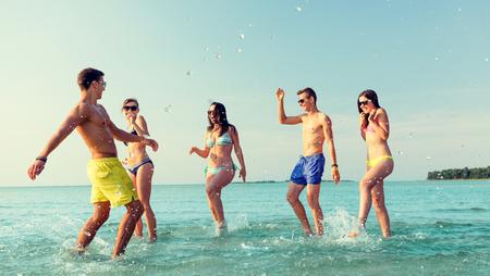 traje de bano: amistad, el mar, las vacaciones de verano, las vacaciones y la gente concepto - grupo de amigos felices que se divierten en la playa