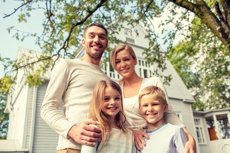 family, happiness, generation, home and people concept - happy family standing in front of house outdoors Foto de archivo