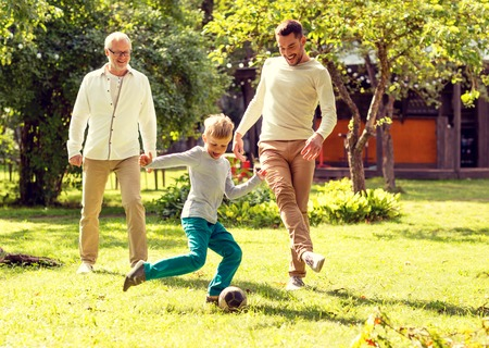grandfather and grandson: family, happiness, generation, home and people concept - happy family playing football in front of house outdoors Stock Photo