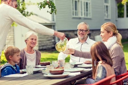 summer house: family, happiness, generation, home and people concept - happy family having holiday dinner outdoors
