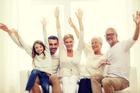 la famille, le bonheur, la production et les gens notion - famille heureuse assis sur le canapé et la hausse des mains à la maison