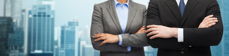 partner: business, people, cooperation and education concept - close up of businesswoman and businessman with crossed arms over city background