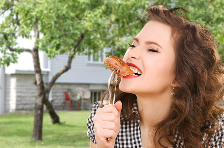 summer diet: people, diet and food concept - hungry young woman eating meat on fork over house and summer garden background Stock Photo