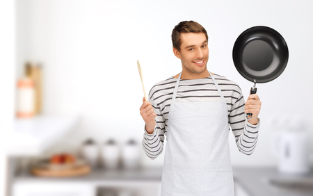 pan: people, cooking and culinary concept - happy man or cook in apron with frying pan and wooden spoon over home kitchen background