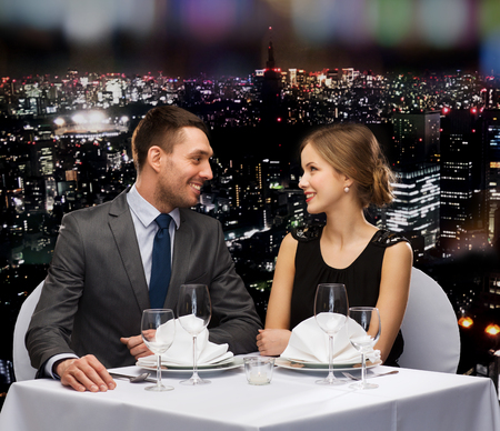 boyfriend: restaurant, couple and holiday concept - smiling couple looking at each other at restaurant