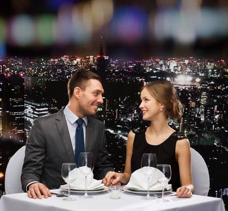 up to date: restaurant, couple and holiday concept - smiling couple looking at each other at restaurant