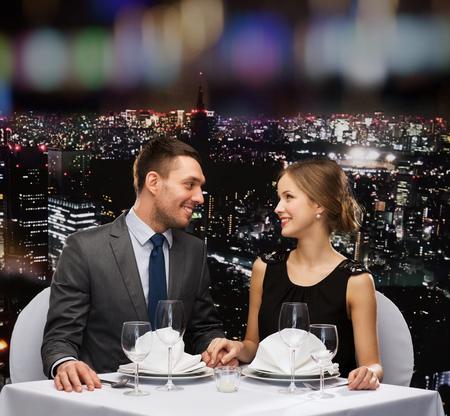 diner romantique: restaurant, couple et concept de vacances - couple souriant regardant les uns les autres au restaurant