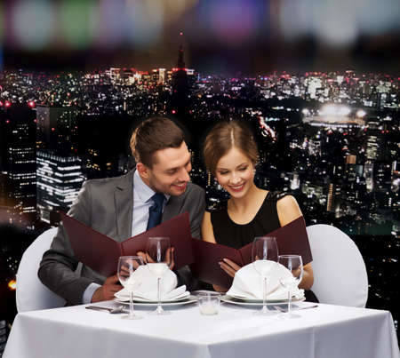 black couple: restaurant, couple and holiday concept - smiling couple with menus at restaurant Stock Photo