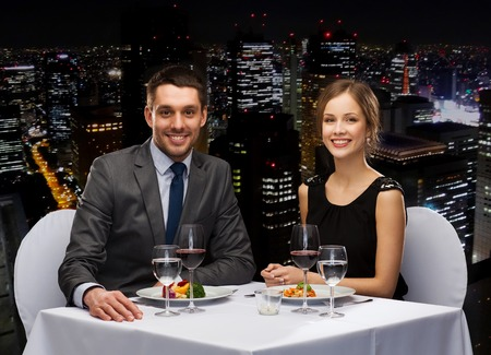 romantic dinner: restaurant, couple and holiday concept - smiling couple eating main course with red wine at restaurant
