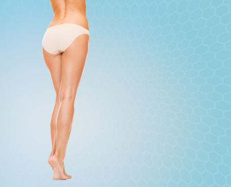 barefoot women: people, health and beauty concept - woman with long legs in cotton panties from back over blue background